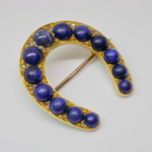 Horseshoe brooch in gold with lapis